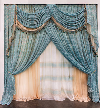 Luxurious green lace curtains in the palace style with fringe and pelmet