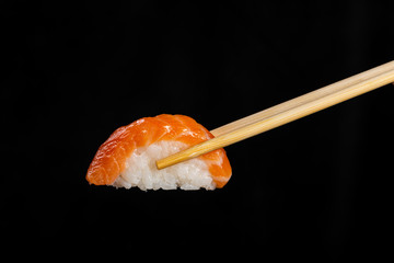 Spoed Foto op Canvas Sushi bar Nigiri Sushi. Woman picking sushi with chopstick. Black background.