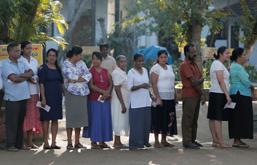 People stand in a line to cast their vote during the presidential election in Colombo
