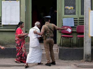 A police officer directs a man to a line at a polling station as he arrives to cast his vote during the presidential election in Colombo