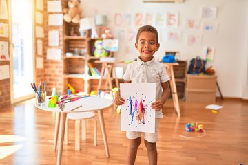 Beautiful african american toddler standing holding draw smiling at kindergarten