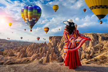 Wall Mural - Beautiful girl standing and looking to hot air balloons in Cappadocia, Turkey.