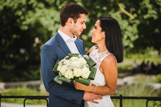 A happy couple on their wedding day. A French European groom and a Latin American (Peruvian) bride, looking at each other and smiling.