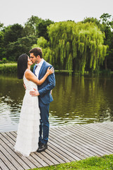 A mixed race/ethnicity couple kiss in front of a pond on their wedding day