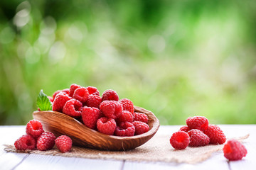 Ripe fresh raspberry in wooden rustic bowl on table. Fotobehang