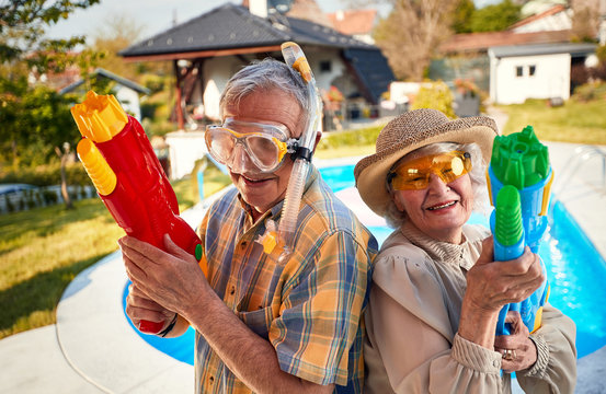 crazy senior people have fun on vacation playing with  water gun