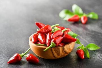 Aluminium Prints Hot chili peppers Hot pepper in wooden bowl on dark stone table. Chili red peppers and green leaves on black background.