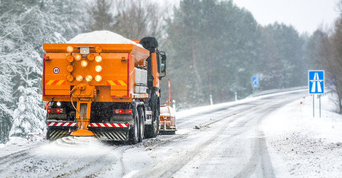 Snow plow on highway salting road. Orange truck deicing street at snowing time. Crystals dropping on asphalt. Maintenance winter vehicle in action.