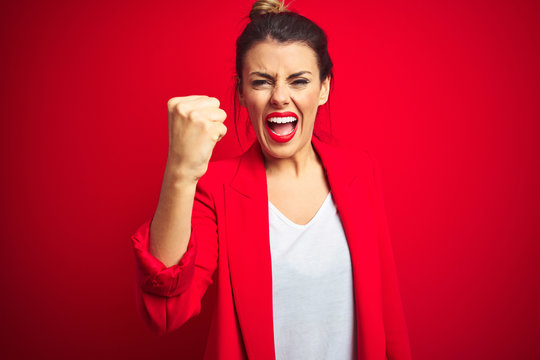 Young beautiful business woman standing over red isolated background angry and mad raising fist frustrated and furious while shouting with anger. Rage and aggressive concept.