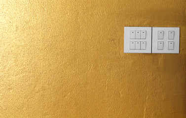Electricity switch on the wall is gold.