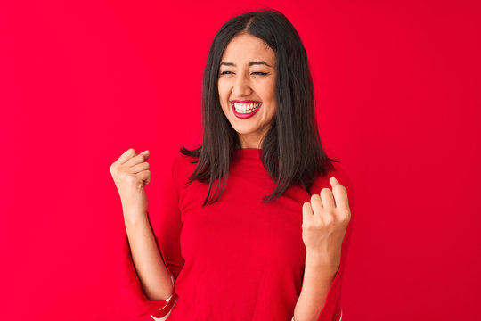 Young beautiful chinese woman wearing casual dress standing oer isolated red background very happy and excited doing winner gesture with arms raised, smiling and screaming for success. Celebration