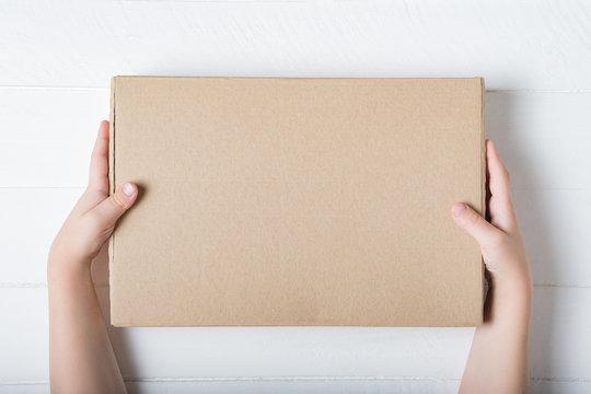 Rectangular cardboard box in children's hands. Top view, white background
