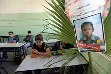Classmate of Palestinian schoolboy Waseem Abu Malhous reacts as Abu Malhous' picture is seen on his chair in his classroom in a school in the central Gaza Strip