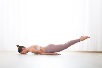 Fotomurales - Portrait of gorgeous active sporty young woman practicing yoga in studio. Beautiful girl practice Poorna Salabhasana, ful locust yoga pose. Healthy active lifestyle, working out indoors in gym.