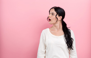 Young woman talking on a pink background