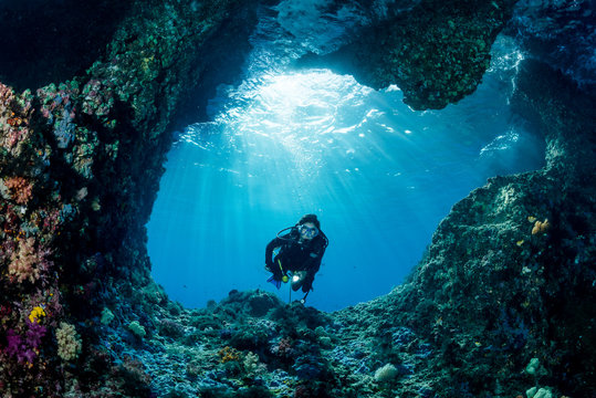 woman diver underwater at the entrance of a cave with sunrays