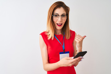 Redhead businesswoman wearing id card using smartphone over isolated white background pointing and showing with thumb up to the side with happy face smiling