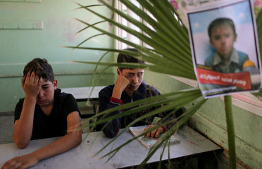 Classmates of Palestinian schoolboy Waseem Abu Malhous, who was killed in Gaza, react as Abu Malhous' picture is seen on his chair in his classroom in a school in the central Gaza Strip