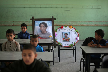 Picture of Palestinian schoolboy Muath Abu Malhous, who was killed in Gaza, is seen on his chair at his classroom in a school in the central Gaza Strip