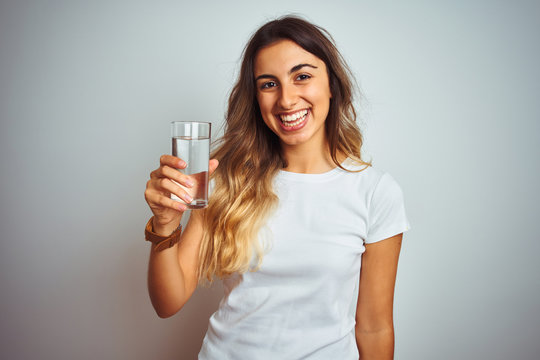 Young beautiful woman drinking a glass of water over white isolated background with a happy face standing and smiling with a confident smile showing teeth