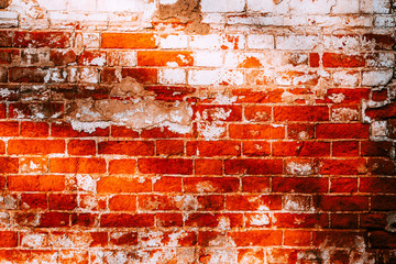 The old brick wall is red and white in the sunlight