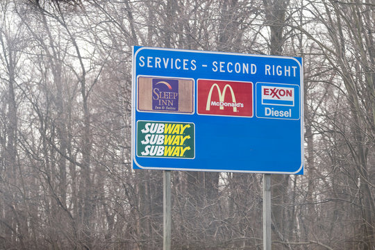 Leesburg, USA - April 6, 2018: Rural Virginia countryside in spring with blue exit sign on highway for food and service such as mcdonalds fast food, sleep in hotel and exxon