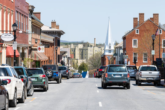 Lexington, USA - April 18, 2018: Historic downtown town city in Virginia countryside Shenandoah mountain village, signs for shops and stores, First Baptist church on main street