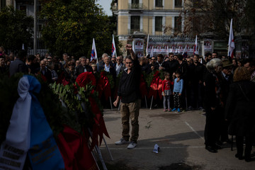 A man raises his fist after laying a wreath on a monument inside the Athens Polytechnic, to mark the 46th anniversary of a 1973 student uprising against the military junta that ruled the country at the time