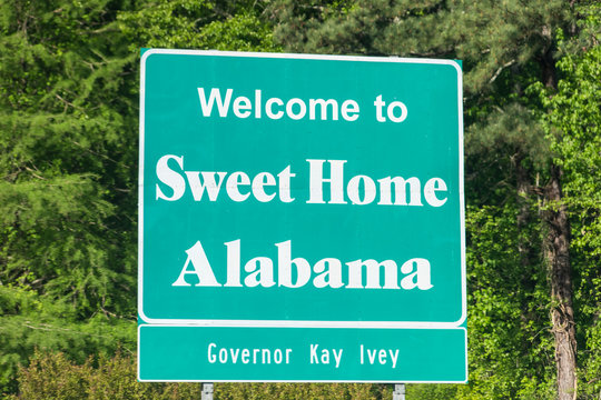 Atlanta, USA - April 21, 2018: Highway road in Alabama with welcome sign and text on street with nobody and sweet home text with Governor Kay Ivey