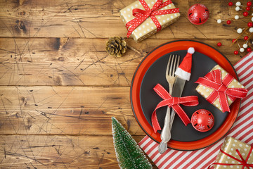Christmas table setting with black plate, gift box and  decorations on wooden background.