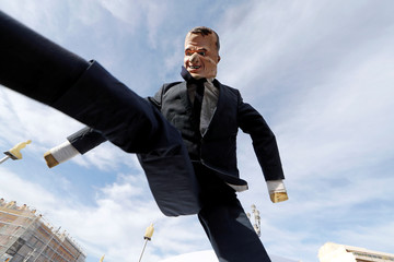 """A puppet depicting French President Emmanuel Macron is tossed into the air during a demonstration to mark the first anniversary of the """"yellow vests"""" movement in Nice"""