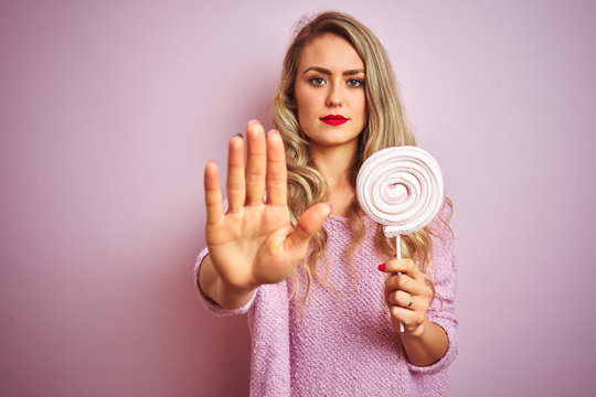 Young beautiful woman eating sweet candy over pink isolated background with open hand doing stop sign with serious and confident expression, defense gesture