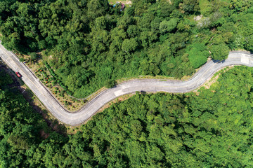 Spoed Fotobehang Luchtfoto Aerial view drone shot top view of Asphalt road curve on mountain tropical rainforest with mountain peaks