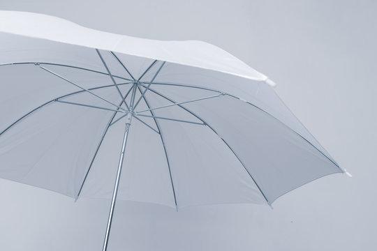 Bottom view of open white umbrella on white background