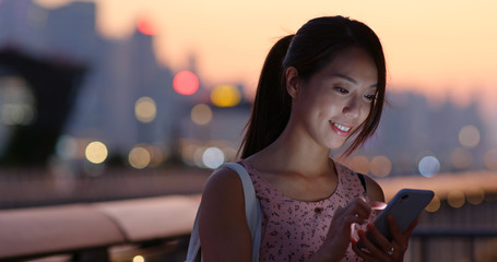 Wall Mural - Woman use of mobile phone at beautiful sunset time