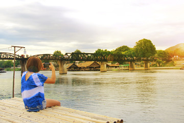 oung female tourists taking pictures of the Bridge over the River Kwai with a mobile phone in Kanchanaburi, Thailand. The bridge was built during World War 2 by Japanese prisoners of war.