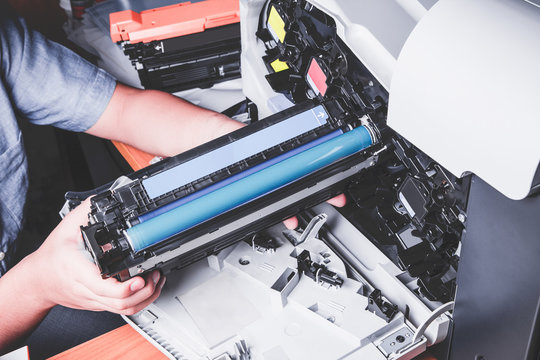 Business man or technician is checking and changing the printer equipment cartridges tone of laser jet multi function printer in the office. Close-up shot of CMYK ink cartridges for laser printer.