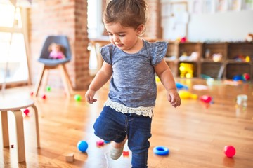 Beautiful toddler standing around lots of toys at kindergarten