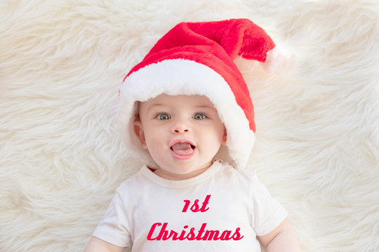 Adorable baby boy wearing red Santa's hat and white t-shirt on a fluffy background with text 1st Christmas