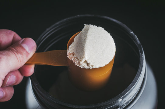 Sports Nutrition Powder. Soluble protein in a measuring spoon in a hand.