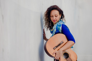 Portrait of young beautiful curly woman posing with guitar