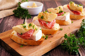 Crostini appetizers with brie cheese, salami and artichokes. Close up on a serving board against a wood background. Party food concept.