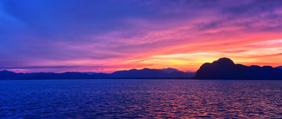 Islands Sunset, Ocean panorama views near Phuket with deep Red, Orange, Purple and Blue, mountains, twilight in Thailand. Including Phi Phi, Ko Rang Yai, Ko Li Pe and other islands. Asia.