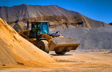 Sand quarry, excavating equipment, bulldozer with heap of sand in background. Selective focus.