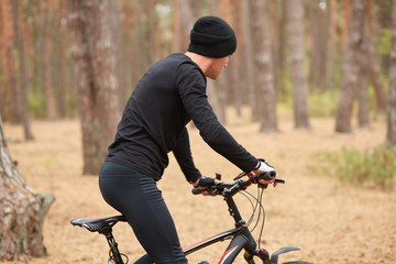 Image of man riding bicycle in forest, spending time in open air. Young guy wearing black track suit, enjoying cycling and beautiful nature. Active recreation, sports and healthy lifestyle concept.