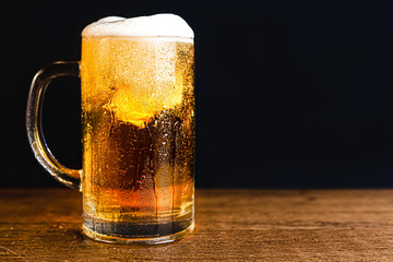 Cold beer with foam in a mug, on a wooden table and a dark background with blank space for a logo or text. Stock Photo mug of cold foamy beer close-up.