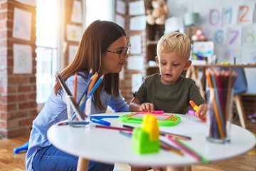 Young caucasian child playing at playschool with teacher. Mother and son at playroom drawing a draw...