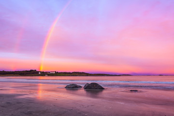 rainbow over beach at farstad in norway