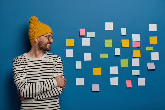 Happy creative male freelance worker stands with hands crossed, wears yellow hat and striped jumper, looks on right side stands at working place, sticky notes for leaving reminder. Teenagers, studying
