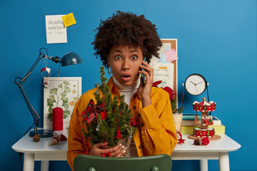 Shocked terrified woman with Afro hairstyle, holds beautiful decorated Christmas tree, forgets to buy something necessary for holiday, makes telephone call, stares at camera, poses near workplace